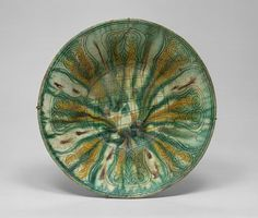 Bowl with green, yellow, and brown splashed decoration, 10th century  Found at Iran, Nishapur, Sabz Pushan, Well in Room 2, Lower Level  Earthenware; white slip, incised and splashed with polychrome glazes under transparent glaze (sgraffito ware)