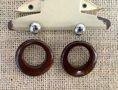 Vintage Mod brown hoop clip on earrings, not signed . silver tone metal ball with inch diameter brown plastic hoop dangling from that . Vintage Earrings, Clip On Earrings, Beer Glass Set, Mod Girl, Message Card, Anklets, Trending Outfits, 1970s, Hoop