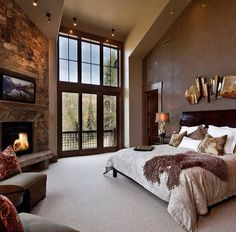 bedroom, stone fireplace, beige carpet, beige and brown bedding, brown accent wall, floor to ceiling windows natural lighting, sitting area