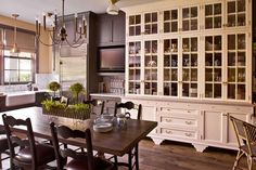 In the kitchen, a wall oven, range, warming drawer, and microwave, all by Wolf, refrigerators by Sub-Zero, and a Murano-glass chandelier found on eBay; the custom-made cabinetry is painted in Benjamin Moore's Night Shade, and the floor is paved in cement tiles from Mission Tile West.