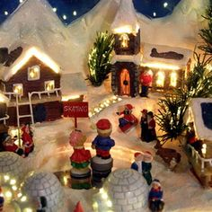 Buildings and figurines on a Christmas village platform.