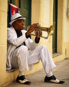 When you think of Cuba music is one of the things that pops up   Walk around and enjoy live music everywhere! Guitar saxophone and trumpet Cubans play and feel the music!   In Havana Vieja we spotted this gentleman. He looks just perfect  with his cool suit and Cuban flag. And his music was great too  by onajourney.nl