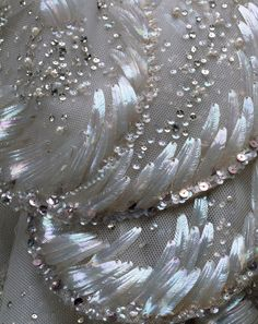 "'Venus' Evening Dress (Detail)  Christian Dior 1949    Autumn/Winter 1949    This extraordinary ball gown by Christian Dior, of foggy gray silk tulle, arrayed with an overlay of scallop-shaped petals, is called ""Venus."" The bodice and shell forms of its skirt are embellished with nacreous paillettes and sequins, iridescent seed beads, aurora-borealis crystals, and pearls. The glittering overskirt and train adumbrate both the seashell motif and the crescent wave patterns of Botticelli's…"