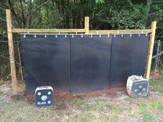 Started off with a frame about 14 feet wide and 6 feet across. used lead pipe and small fence clamps to hang three horse stall mats. Then just in case, ran the cable through the pipe, pulled tension and mounted them to rings for extra support. Archery Range, Archery Hunting, Bow Hunting, Archery Training, Backyard Fences, Garden Fencing, Fence Landscaping, Archery Target Stand, Shooting Targets