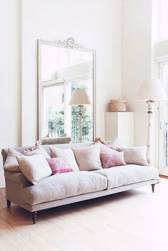Pale pink couch and oversized mirror