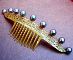 """A very wide hair comb from the Art Deco period decorated with faux pearl balls.    SIZE: 3 ins h x 9 ins w (7.5 x 23 cms)    APPROXIMATE DATE: 1920s  This type of comb is sometimes called a """"shingle comb"""" and would be worn low on the back of the head, often holding a wide roll of hair at the base of the neck. @Deidra Brocké Wallace"""
