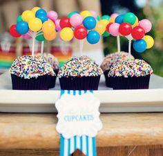 cupcakes avec des sprinkles multicolore et des sucettes comme cake toppers