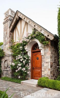Old World Tudor style cottage. Flowers grow around the entrance to this charming stone guest house. Tudor Cottage, Old Cottage, Cottage Style, Garden Cottage, Cottage Farmhouse, Storybook Homes, Storybook Cottage, Stone Cottages, Cabins And Cottages