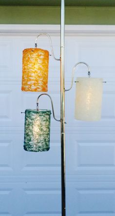 Tension pole lamp with spaghetti string cylinder shades.