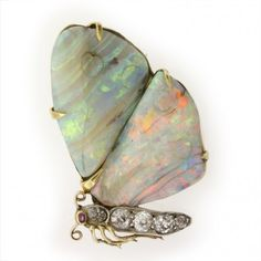 A Victorian opal and diamond butterfly brooch with carved opal wings on a pierced and engraved gold back with old brilliant-cut diamond-set body and ruby head, the diamonds weighing approximately 0.80 carats, circa 1880,