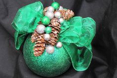 Green ornament decorated with pine cones and miniature ornaments