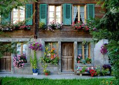 House in Switzerland- love the shutters,wood & hanging flower baskets