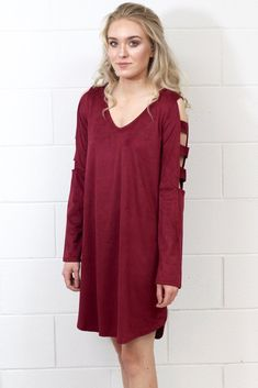 Super soft suede dress with a v-neckline and long sleeves that feature a cut-out ladder pattern. Shift style with slight slit creating a bit of a hi-lo look at the u-hemline.