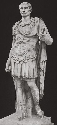 Roman: Statue of Julius Caeser wearing molded body armor and leather skirt customary of military attire, as well as the paludamentum, a cape that is pinned at one shoulder by a gold fibula to signify social status. (worn only by emperors)
