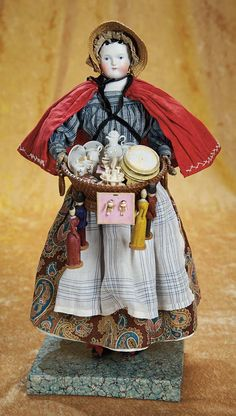 German Bisque Peddler Lady with Basket of Novelties and Wares. Circa 1870. Basket, miniature leather books, porcelain dishes dolls