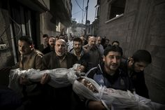 This Photo Will Break Your Heart;  The winner of the World Press Photo of the Year, showing a group of grieving men carrying dead children through the streets of Gaza City, is stunning and tragic.