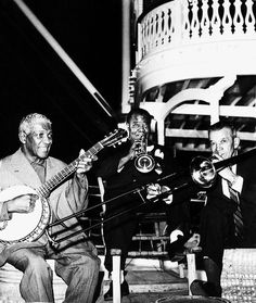 Johnny St. Cyr (banjo), Louis Armstrong (trumpet), and Kid Ory (trombone) playing on the Mark Twain Riverboat at Disneyland Park in the 1960s.