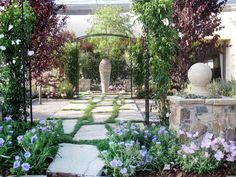 ~design by Shellene Mueller, wrought-iron garden accents, loose mounds of flowers and a low stone wall frame the entrance to a serene patio garden...