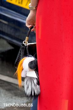 On the Street: couture Day 1 (Jean Paul Gaultier show). Despite the pouring rain in the streets of Paris, you can feel the sensual atmosphere around the couture fashion show by Jean Paul Gaultier (fall 2014). Read more http://trendbubbles.nl/not-dutch/ #streetstyle #street #style #handbag #accessories A Fendi mini Karl Lagerfeld fur mascotte: Bag Boy #Karlito with little orange ponytail