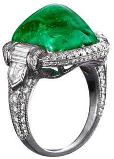 Superb sugarloaf emerald and diamond ring. This platinum ring centers an exactly 10.69 ct. emerald which is accompanied by a report confirming it is Colombian in origin; this center stone is accented with fine fancy cut diamonds. Via 1stdibs.