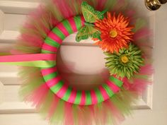 Summer wreath in brilliant neon green and fluorescent pink tulle with flowers and butterfly accents made on a 12 inch foam wreath