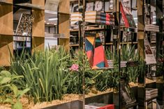 Grasses and flowers are planted on the two existing tables to illustrate the landscape of Durslade farm in Somerset, England. Popup bookstore installation by Dongji Architects inspired by old granary sheds. #grass #flowers #planter #landscapingideas #landscapearchitecture #popup #bookshop #installation #inspirational #architect #shanghai