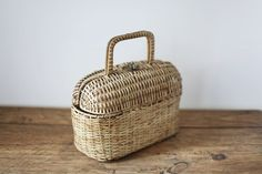 Circa 1950.Small wicker basket bag with two handles and metal clasp.Some vinyl linng on the inside and plastic feet on the bottom.Good vintage condition.MEASURES:20 x 28 x 13cm {excluding handles}