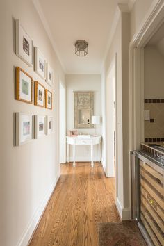 The hallway leading from the living room to the den is complete with a built-in bar and a sweet gallery photo wall featuring Laura, Marshall, and Sadie at home and on vacation. Laura ordered the frames for the gallery on Framebridge.