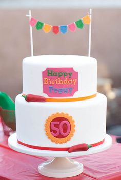 Fiesta Birthday Cake with Edible Bunting - This fondant covered cake features fondant chil peppers and a fondant papel picado bunting cake topper.