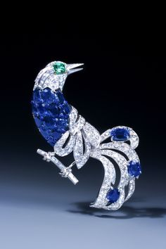 "sapphire, emerald, and diamond bird of paradise brooch by Cartier, mounted in platinum and gold. Signed ""Cartier Paris"" and numbered, the piece was made in Paris, circa 1950."