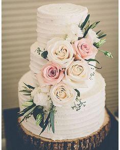 Rustic wedding cake adorned with blush florals on wood slice cake stand #weddingcake #rusticwedding #rusticweddingcake #floralweddingcakes