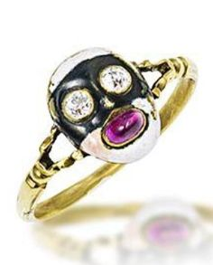 An 18th century antique gold, enamel and gem-set carnival ring. The bezel designed as a white enamel face with old brilliant-cut diamond eyes and a cabochon ruby mouth, wearing a black enamel domino mask, mounted in yellow gold. #antique #ring