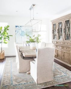 A coastal dining room with linen dining chairs, wood dining table, a linear Darlana pendant light, vintage style rug, large wood hutch, blue abstract art and a fiddle leaf fig tree. Large Dining Room Table, Linen Dining Chairs, Country Dining Rooms, Dining Room Design, Kitchen Design, Small Space Living, Room Decor, Fiddle Leaf, Fig Tree