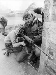 A British soldier lets a young boy look through the sights of his rifle in Belfast, c.1981