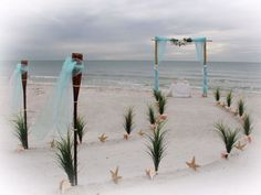 beach wedding aisle A two post arch with blue drapes and a flower garland at the end of a special Suncoast Weddings sweeping aisle lined with grasses, conch shells and starfish Beach Wedding Locations, Beach Wedding Bouquets, Beach Theme Wedding Invitations, Beach Wedding Centerpieces, Beach Wedding Reception, Beach Ceremony, Wedding Favors For Guests, Wedding Reception Decorations, Beach Weddings