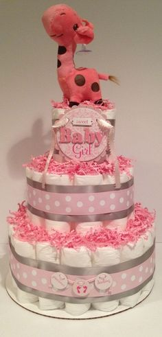A diaper cake will make a beautiful lasting impression at any baby shower! Perfect centerpiece or welcome baby gift for expecting parents! Diaper Cake includes: - (40) Size 1 Diapers (Bottom and Top Tier) - (17) Size 2 Diapers (Middle Tier) - (1) Plush Giraffe - (2) Girl Decals ** Can be made with all one size diaper** - Just specify when purchasing. Made with: - 12 White Cake Board - Decorative ribbons, and Pink crinkle paper. ** Measures about 14 tall ** All Diapers Cakes are placed ...