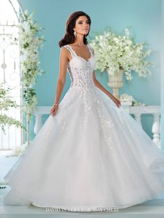 This tulle over organza and satin full A-line gown with hand-beaded re-embroidered lace features illusion and lace tapered shoulder straps.