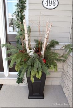 Christmas Urns  top  black urns with a grapevine wreath, a boxwood garland then filled the urn with fresh pine, birch branches.