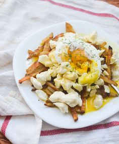 Eggs Benedict Poutine. Seasoned baked French fries topped with fresh cheese curds, hollandaise sauce and a fried egg.
