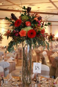 The design team at Lipinoga Florist created a gorgeous autumnal setting for this fall wedding at Westwood Country Club in Williamsville, NY.  Tall cylinder vases filled with curly willow were topped with an extravagant display of fall flowers, greenery and berries to lend a rustic yet elegant touch. Getting married? Call for a personal consultation: (716)759-6563 or visit our blog to see more real weddings by the Lipinoga Team: www.BuffaloWeddingAndEventFlowers.com