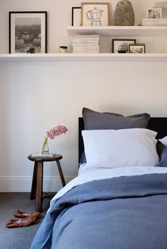 White, grey, neutral bedroom. Shelves over the bed. Home of Nicolle Sullivan of CULTIVER, via The Design Chasers
