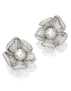 PAIR OF 18 KARAT WHITE GOLD, CULTURED PEARL AND DIAMOND EARCLIPS The flowerheads centered by two cultured pearls measuring approximately 12.6 mm, the petals set with numerous round diamonds weighing approximately 7.70 carats.