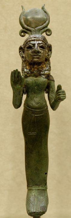 A Phoenician goddess, wearing a Hathor-style headdress, raises a hand in a gesture of blessing. At the Louvre.