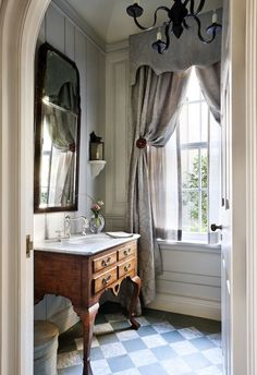 Beautiful millwork and arched doorway set the stage for this charming Sea Island, Georgia powder room with interiors by David Guilmet Design.