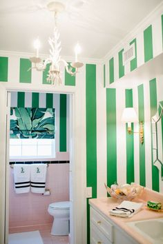 Cant afford to change those pink tiles and fixtures? No worries, add some bright green stripes and jungle inspired accents and voila, Palm Beach Chic bathroom!