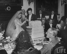 Cayetana, Duchess of Montero and Don Luis Martinez cutting their wedding cake as her father, the Duke of Alba, looks on. October 1947