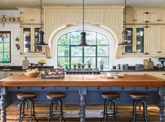 Rustic finishes and cabinetry inspired by antique furniture give this inviting space layers of true-blue country charm in this kitchen.