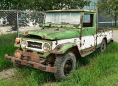 """Toyota Land Cruiser """"A beat up old Toyota Land Cruiser pickup (long off the road)"""""""