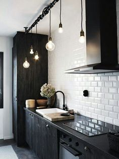 Pair sleek black cabinets with glossy white tiles for a striking contrast.
