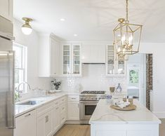 This classic white kitchen has painted shaker cabinetry and quartz countertops and warming the space are wood floors and accents of gold and silver! #interiordesign #interior #design #interiorinspo #designinspo #inspiration #kitchen #kitchendesign #kitcheninspo #kitchenstyle #kitcheninteriors #whitekitchen #cabinetry #cabinetinspo #blondewood #blondewoodflooring #quartzcountertops #counterinspo White Coastal Kitchen, Small White Kitchens, White Shaker Kitchen, Classic White Kitchen, Shaker Style Kitchens, Home Kitchens, Coastal Kitchens, Kitchen And Bath Design, Modern Kitchen Design